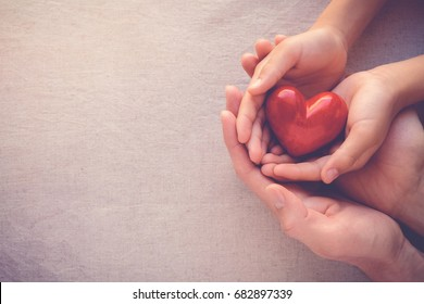 adult and child hands holding red heart, health care, donate and family insurance concept,world heart day, world health day, CSR concept, adoption foster family