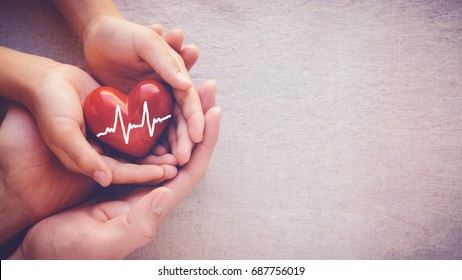 adult and child hands holding red heart with cardiogram, health care love and family insurance concept, world heart day