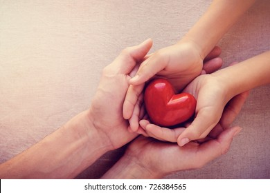 adult and child hands holding red heart, health care love, give, hope and family concept, world heart day,world health day