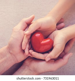 adult and child hands holding red heart, health care love, give, hope and family insurance concept