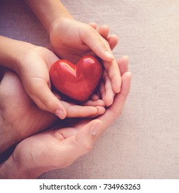 adult and child hands holding red heart, health care love and family concept, world heart day