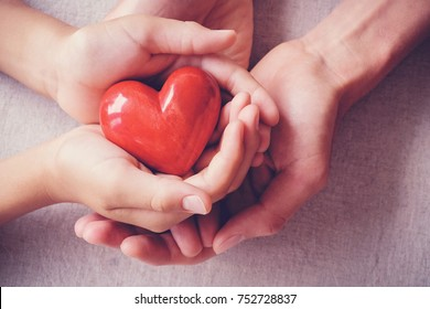 adult and child hands holding red heart, health care, love, organ donation, family insurance and CSR concept
