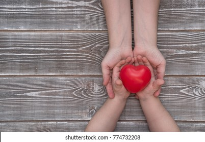adult and child hands holding red heart, health care, insurance and family concept, world heart day