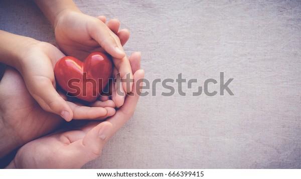 Erwachsene und Kinder, die ein rotes Herz halten, Gesundheitsfürsorge, Liebe und Familienversicherung Konzept, Weltherztag, Weltgesundheitstag, Adoptivfamilien, internationaler Familientag