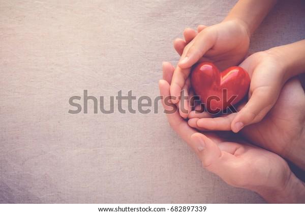 成人及兒童雙手握著紅心、健康護理、捐贈及家庭保險概念、世界心臟日、世界衛生日、CSR 概念、領養家庭