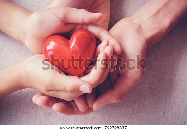dospělé a dětské ruce držící červené srdce, zdravotní péče, Láska, dárcovství orgánů, rodinné pojištění a koncepce CSR, Světový den srdce, Světový den zdraví