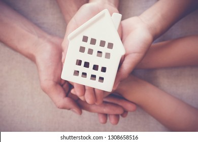 Adult and child hands holding white house, family home, protecting home and homeless shelter, eco green sustainable living concept, international day of families