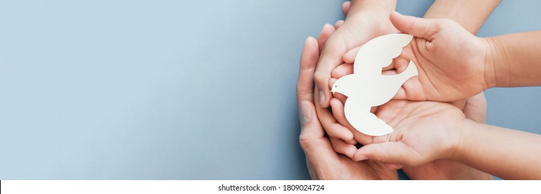 Adult and child hands holding white dove bird on blue background, international day of peace or world peace day concept, sustainable consumption, csr responsible business concept - Shutterstock ID 1809024724