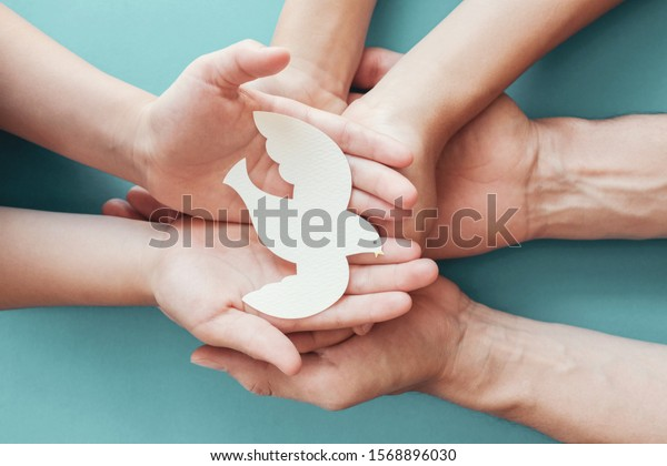 Adult and child hands holding white dove bird on blue background, international day of peace or world peace day concept, sustainable consumption, csr responsible business, animal rights, hope concept