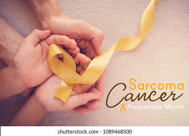adult and child hands holding yellow gold ribbon, Sarcoma cancer Awareness month