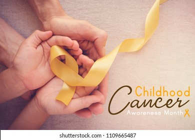 adult and child hands holding yellow gold ribbon, Childhood cancer Awareness month