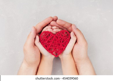 Adult and child holding red heart in hands top view. Happy family relationships, health care, pediatric cardiology concept.