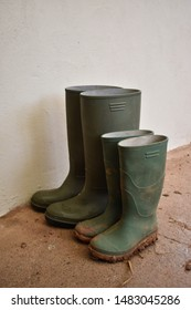 Adult and child pairs of green wellington farmer boots waiting outside the house. Wellies are against a plain white wall.