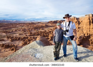 An adult and a child standing in front of Goblin Valley State Park, Utah, US