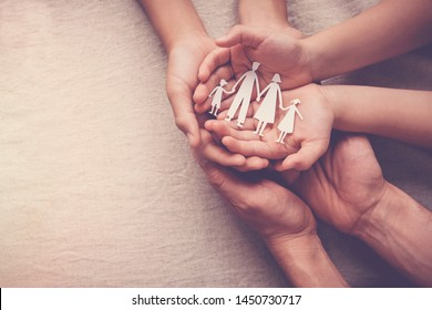 Adult and children hands holding paper family cutout, family home, foster care, homeless support, international day of families concept, world mental health day