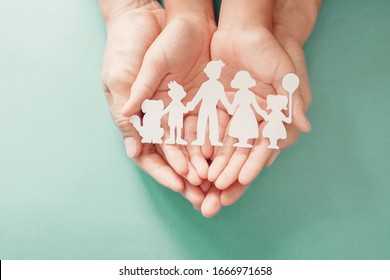 Adult and children hands holding paper family cutout, life insurance planning, adoption, foster care, homeless support, family mental health, family wellness, social distancing concept