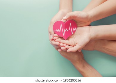 Adult and children hands holding red heart with cardiogram, health care, organ donation, family life insurance, world heart day, world health day, praying concept