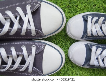 Adult and children's sneakers next to the green grass.Top view