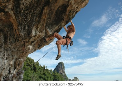 Adult climbing hard overhanging wall in Krabi, Thailand.