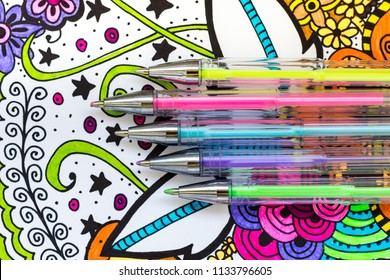 Adult coloring book, new stress relieving trend. Art therapy, mental health, creativity and mindfulness concept. Adult coloring page with pastel colored gel pens, Flat lay background.