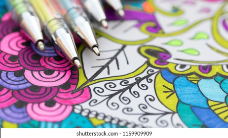 Adult coloring book, new stress relieving trend. Art therapy, mental health, creativity and mindfulness concept. Adult coloring page with pastel colored gel pen close up.