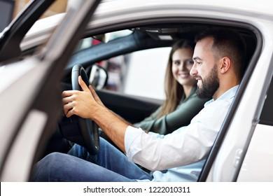Adult couple choosing new car in showroom