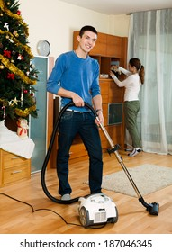 Adult couple cleaning with vacuum cleaner in living room