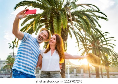 Adult couple dating and having fun in Barcelona at sunset. Man and woman together on a summer sunny day in Barcelona, taking a selfie with palm trees and sun on background. Love and lifestyle concepts