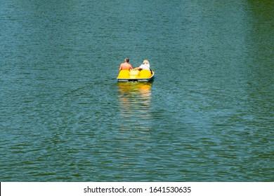 Adult couple driving yellow catamaran on river