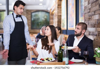 Adult couple expressing dissatisfaction with waiter about a food