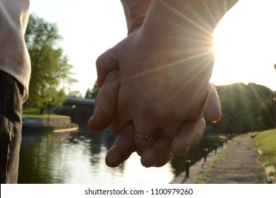 An adult couple hold hands during a romantic sunet walk along the waters edge.