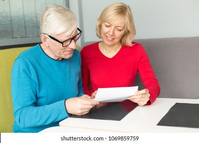 Adult couple make out papers sitting at a table. To sign a pension insurance policy or contract.