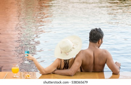 Adult couple relaxing on the edge of  swimming pool in resort spa retreat. Hotel travel vacation. Relaxation concept. Unrecognizable people from behind enjoying summer holidays.