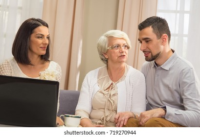 Adult couple and senior lady with open laptop indoors