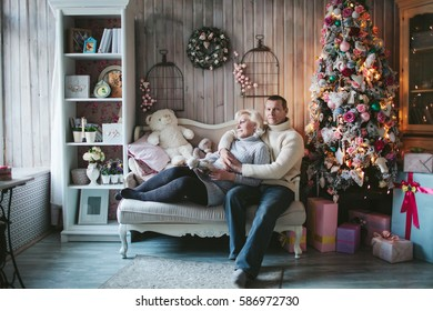 adult couple sitting at the Christmas tree