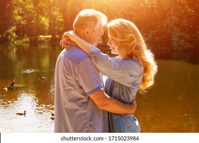 An adult couple stand on the shore of the lake in an embrace in the rays of the setting sun.