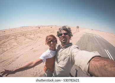 Adult couple taking selfie on road in the Namib desert, Namib Naukluft National Park, main travel destination in Namibia, Africa. Fisheye view.