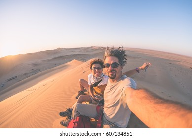Adult couple taking selfie on sand dunes in the Namib desert, Namib Naukluft National Park, main travel destination in Namibia, Africa. Fisheye view in backlight, toned image.