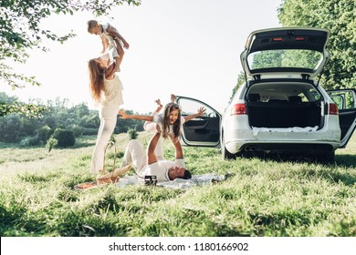 Adult couple with their little children having picnic in the Park Outside the City, Family Weekend Concept, Four People Enjoying Summer