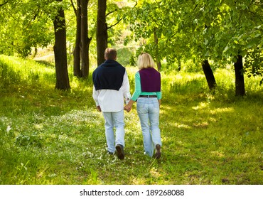adult couple walking through forest with hand in hand