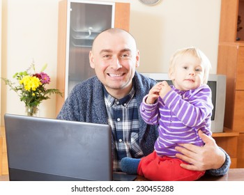 Adult dad sitting at  laptop with  young daughter on his lap