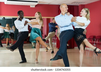 Adult dancing couples enjoying active boogie-woogie in modern studio