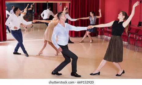 Adult dancing couples enjoying active swing in modern studio