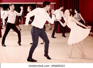 Adult dancing couples enjoying active dance in modern studio