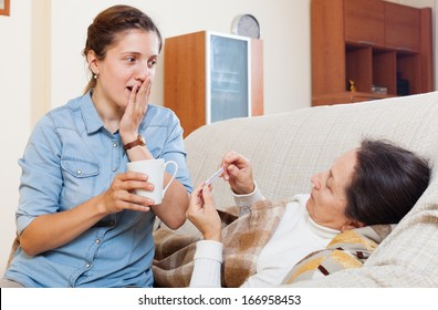 Adult daughter caring for a sick mother who has high temperature