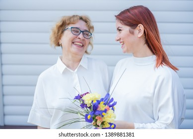 Adult daughter gives flowers to her mother outside, in the courtyard of the house. Spending time together, celebrating at home on weekends. Mothers Day. Warm intergenerational relationships