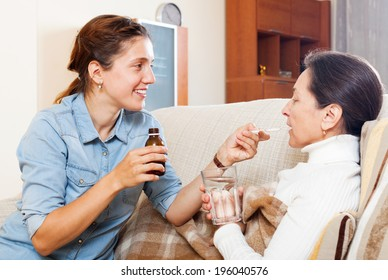 Adult daughter giving the liquid medicament to mature woman at home