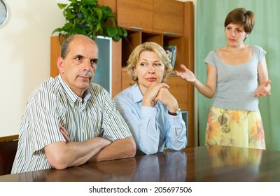 Adult daughter having serious talking with mature parents at home