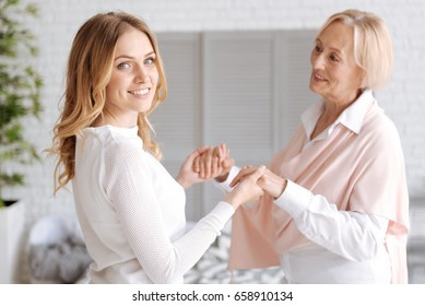Adult daughter holding her mothers hands