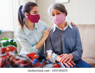 An adult daughter hugs an elderly mother by the shoulders and put on masks to protect against coronavirus - A volunteer visits a pensioner to provide psychological assistance in covid-19 conditions